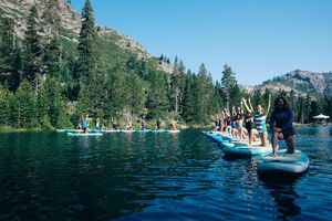 Women doing yoga on stand up paddle boards on a river in Squaw valley