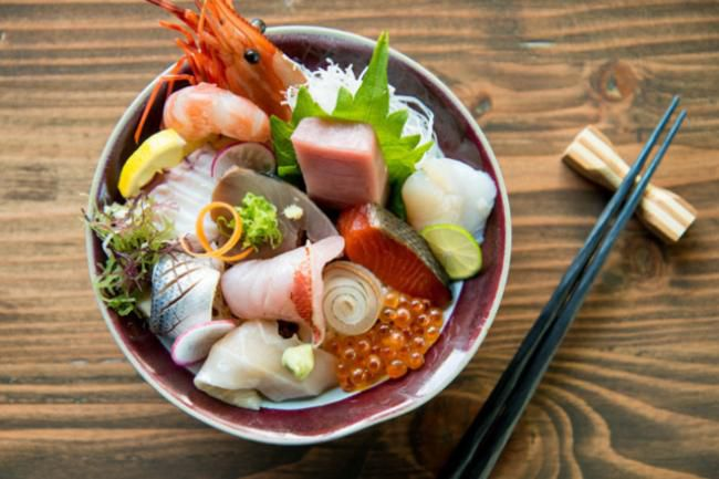 a bowl of raw fish, shrimp and fish eggs with a pair of black chopsticks on a chopstick rest next to it
