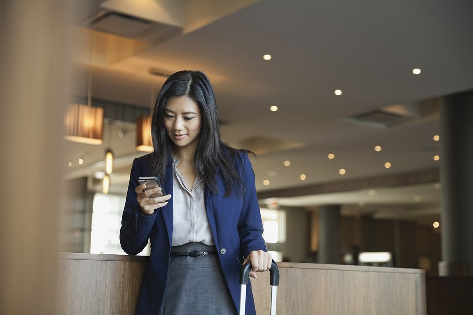 Businesswoman using smart phone in hotel lobby.