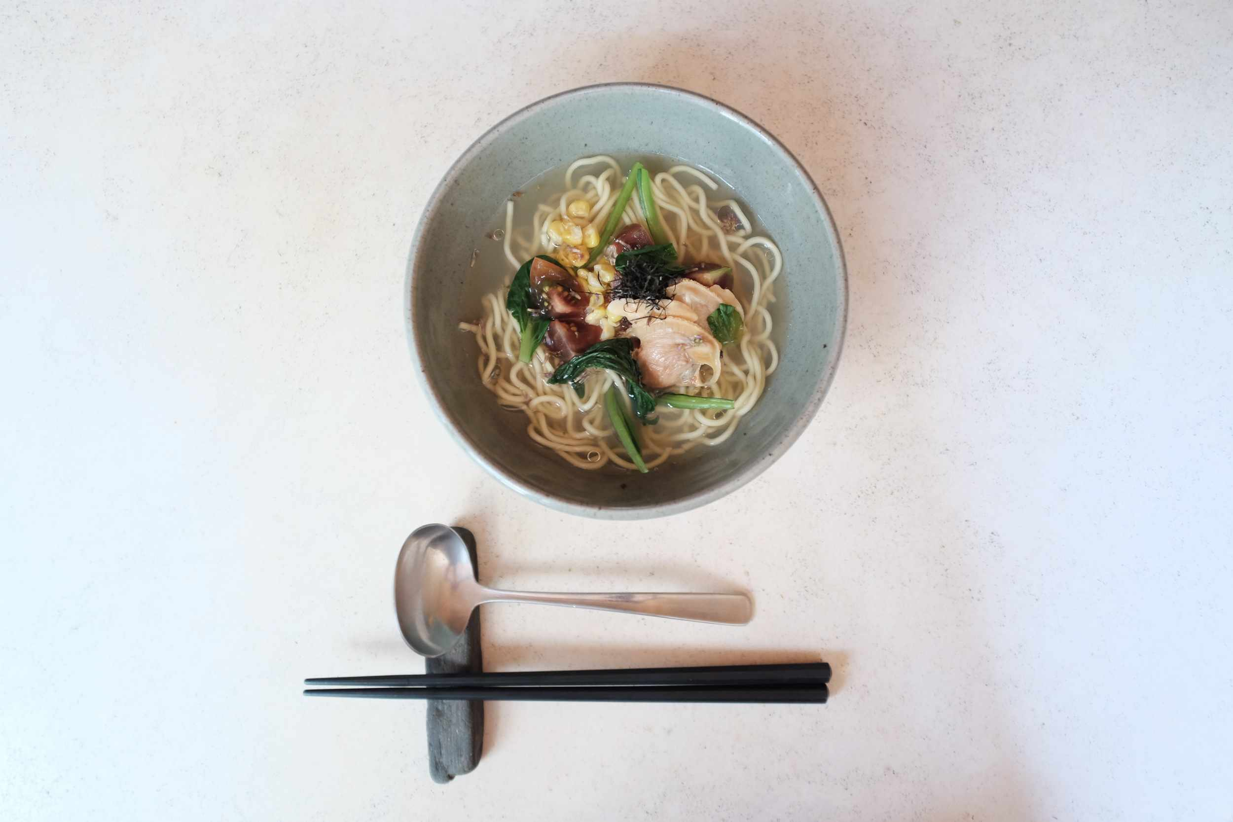 Overhead image of clear broth ramen with clams, spinach, and tomatoes. below the bow there is a pair of chopsticks and a wide spoon on a chopstick rest from YUJI Ramen