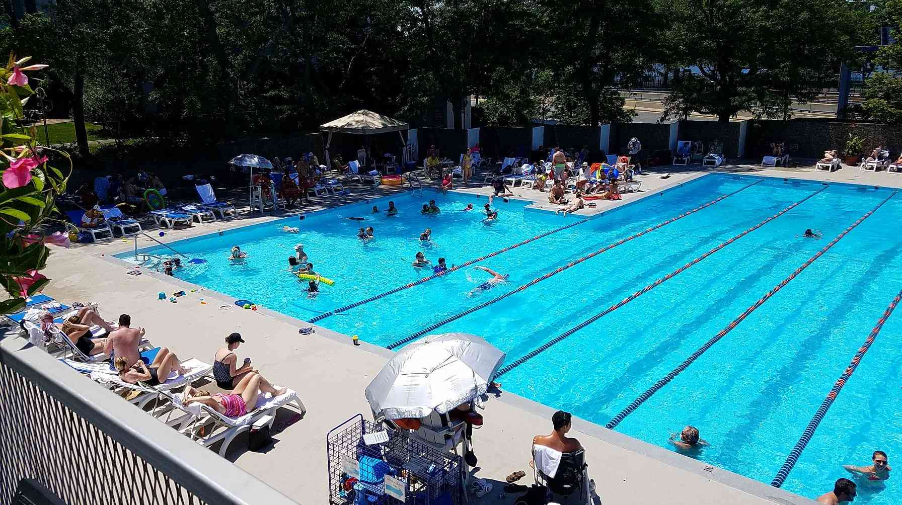 Outdoor pool with several people swimming laps, a bunch of people playing with pool floaties and people sunbathing on pool chairs