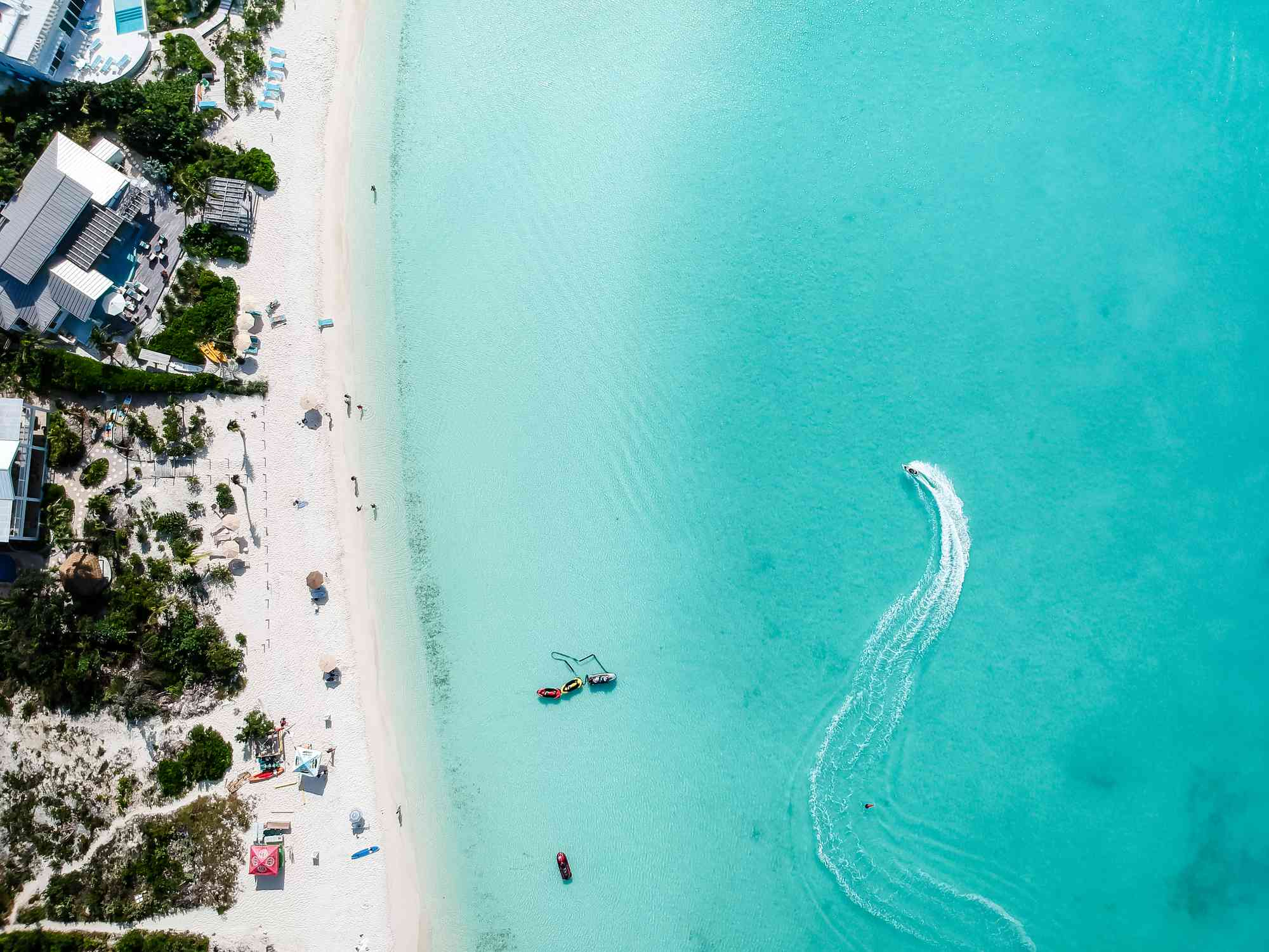 aerial view of a white sand beach and a jet ski in clear blue water