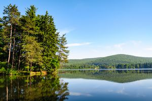 calm lake surface with reflections of surrounding pine trees and hills