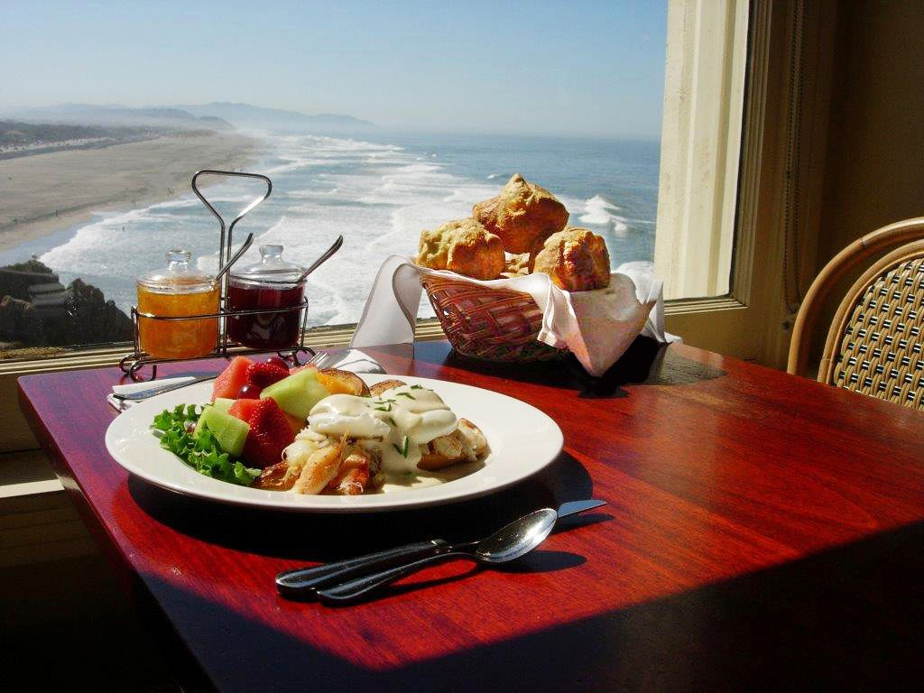 lobster tail and fruit on a plate with a basket of popovers with a view of a beach outside the window