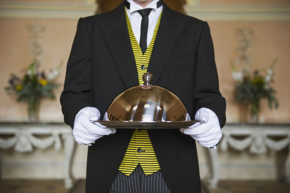 butler holding serving tray in formal parlor
