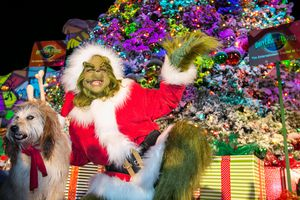 The Grinch poses with a dog near a Christmas tree at Grinchmas at Universal Studios, Los Angeles