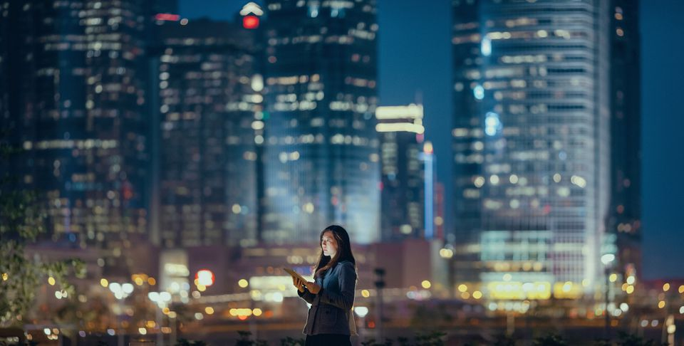 Young businesswoman using digital tablet in Hong Kong financial district