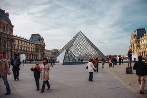 People walking around the outside of the Louvre