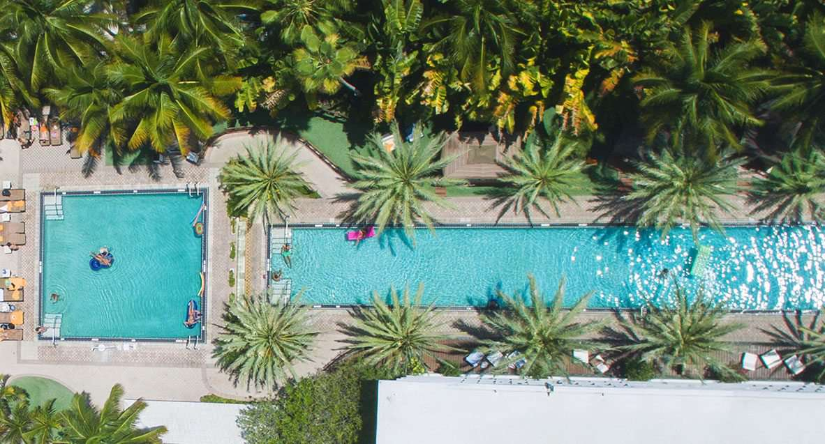 Aerial view of a square pool next to a long, narrow, rectangular pool with trees on the top quarter of the photo