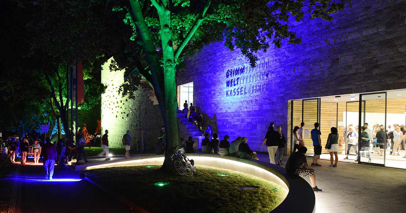 people standing outside the building of GRIMM WELT at night
