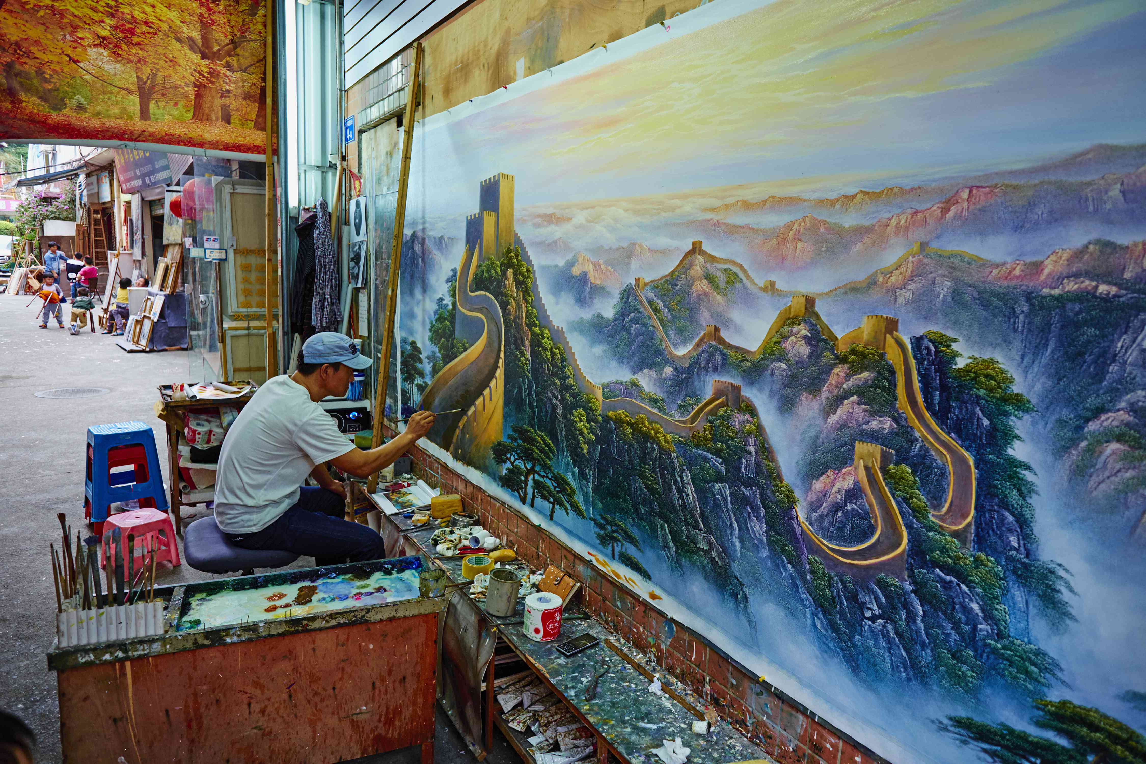 An artist painting mural of the Great Wall of China in Da Fen Village, Shenzen