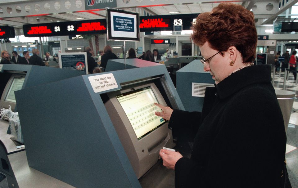 A woman uses a self-service check-in kiosk at Chicago's O'Hare Airport