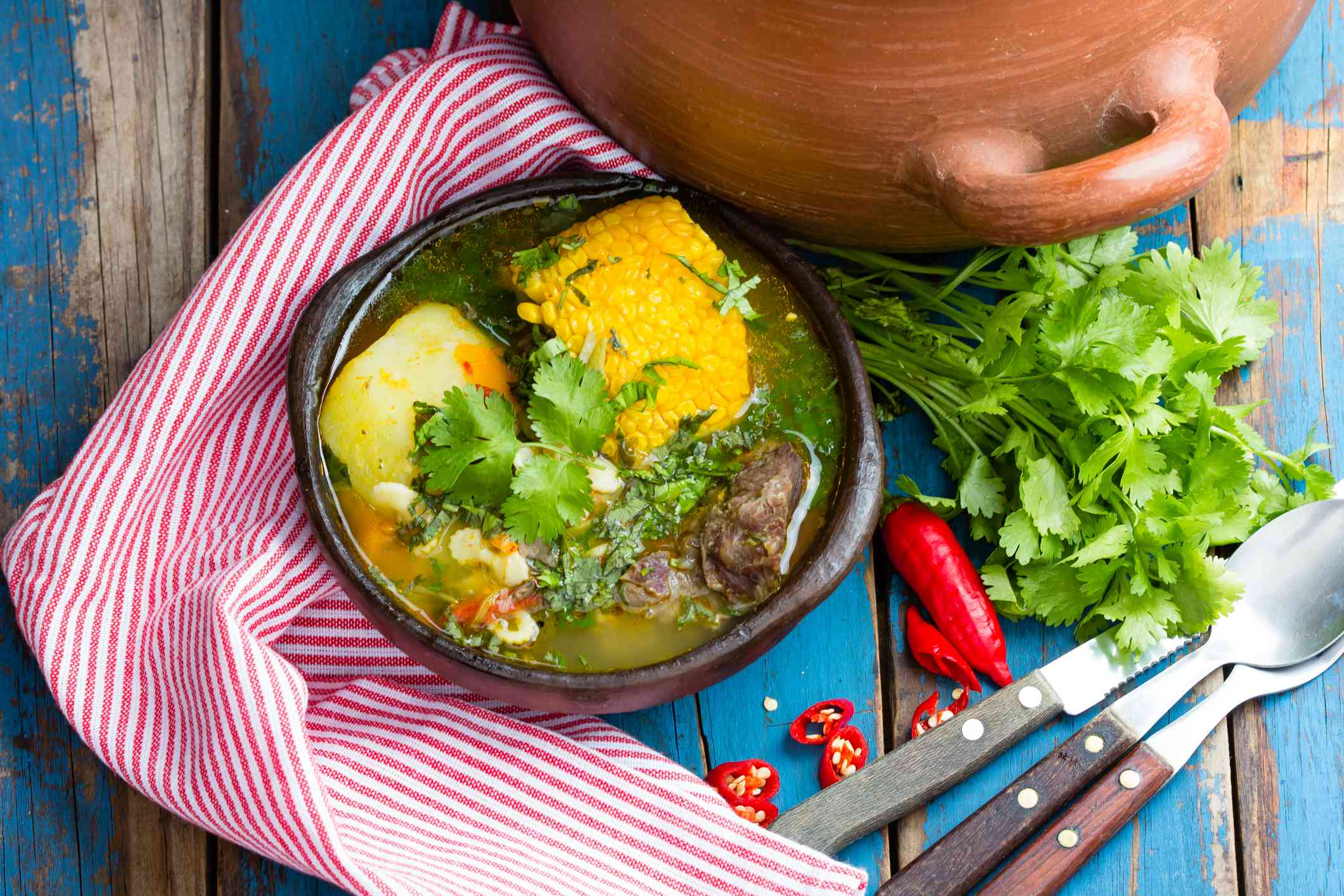 Beef cazuela on a blue table with silverware and towel