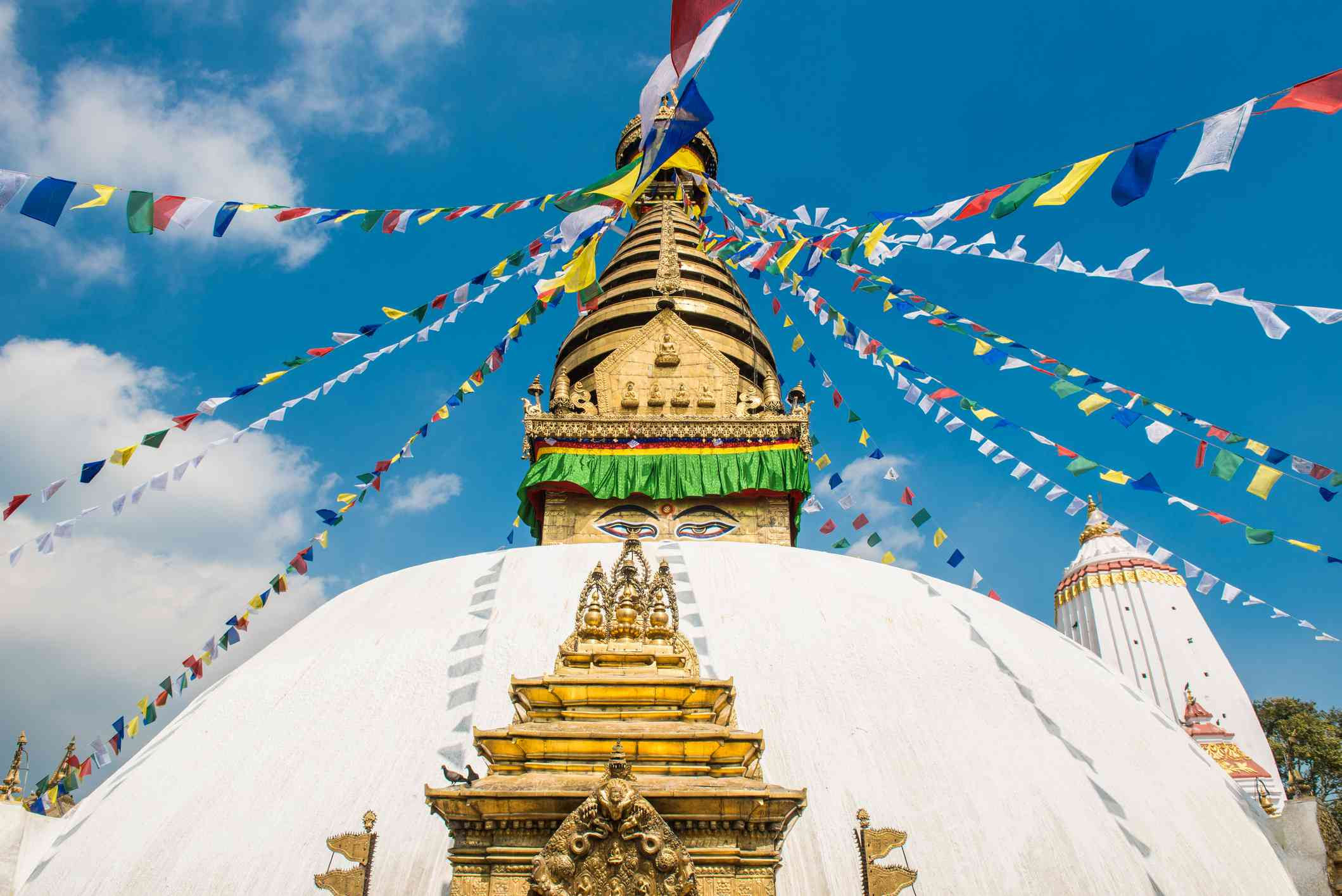 white dome with golden spire and colorful Tibetan prayer flags