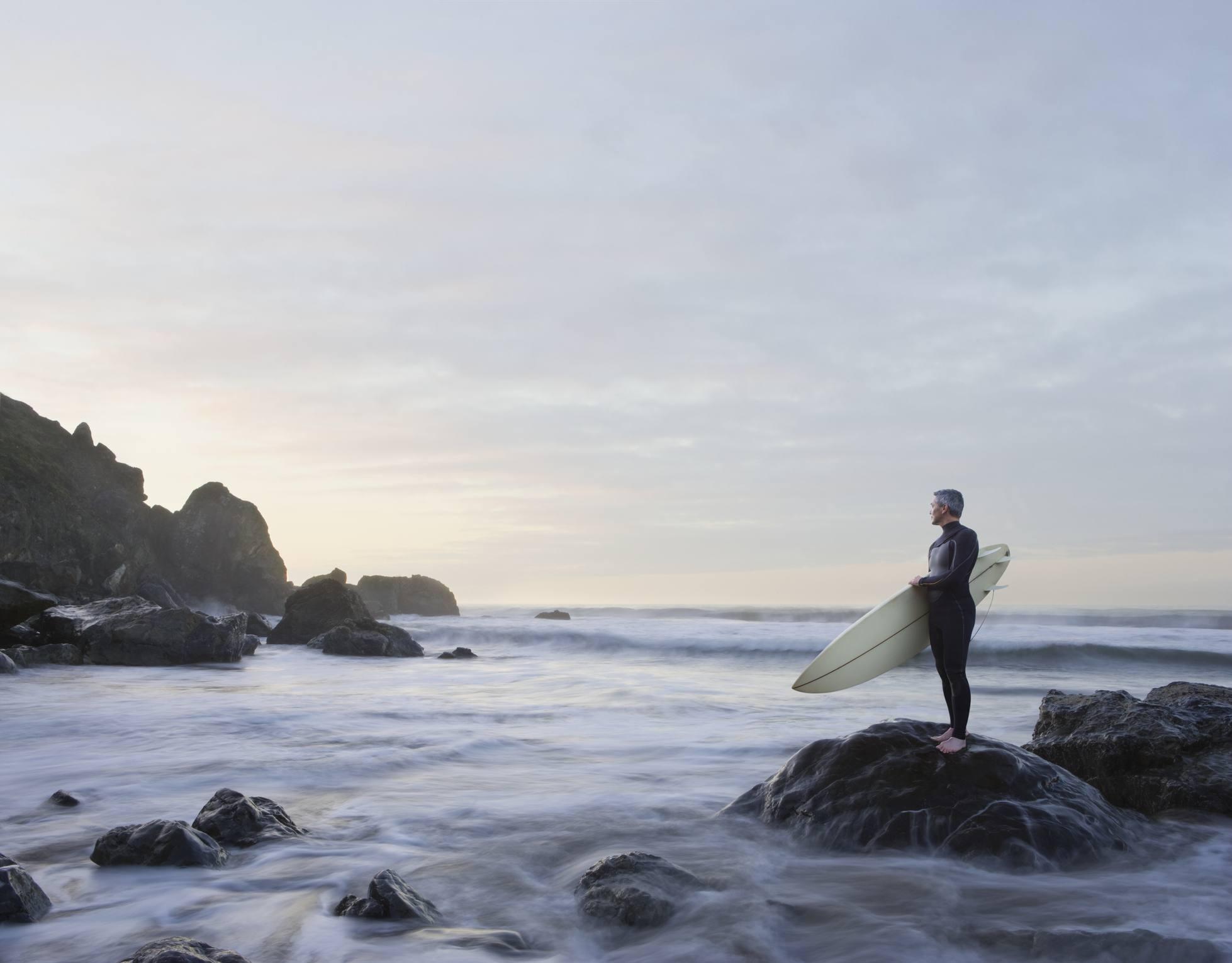 Surfer standing on rock in ocean, Stinson Beach
