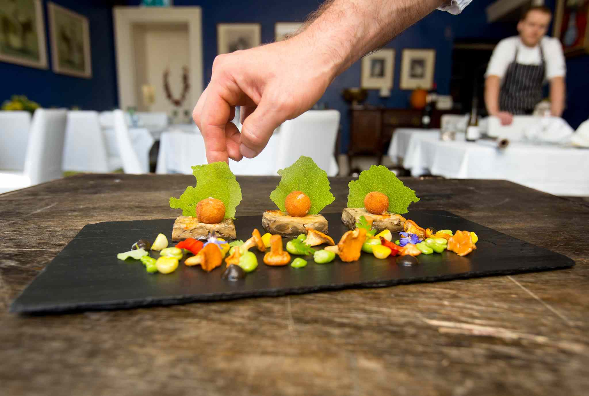 Hand placing green garnish on slate plate