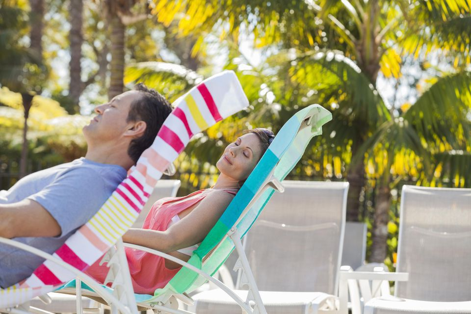 Mature couple relaxing on lounge chairs at resort