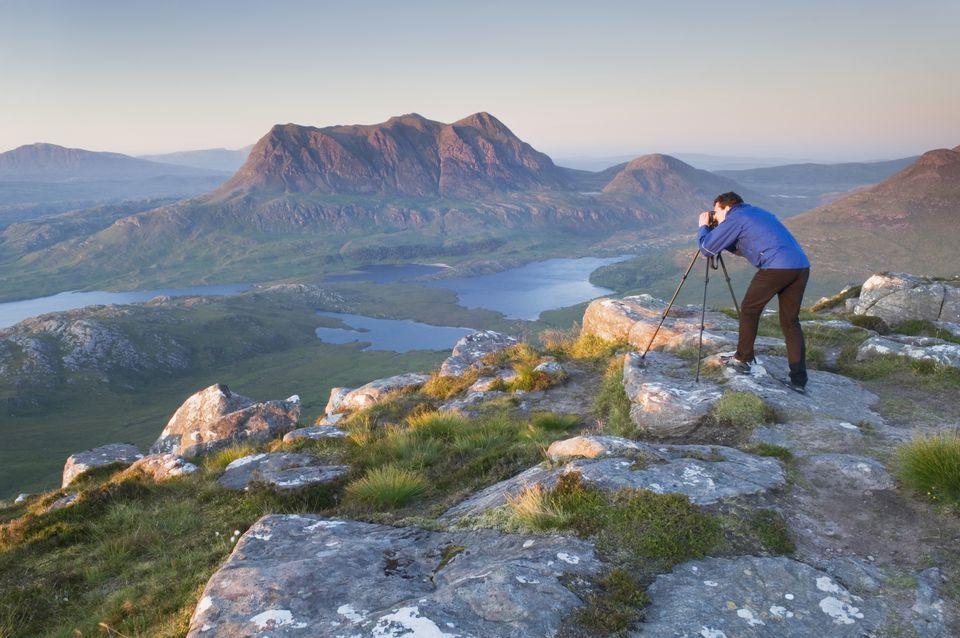 ¿Fotógrafo en la montaña montando una cámara con trípode?
