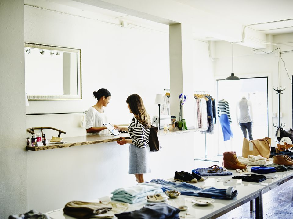 Customer completing transaction on digital tablet in womens clothing boutique