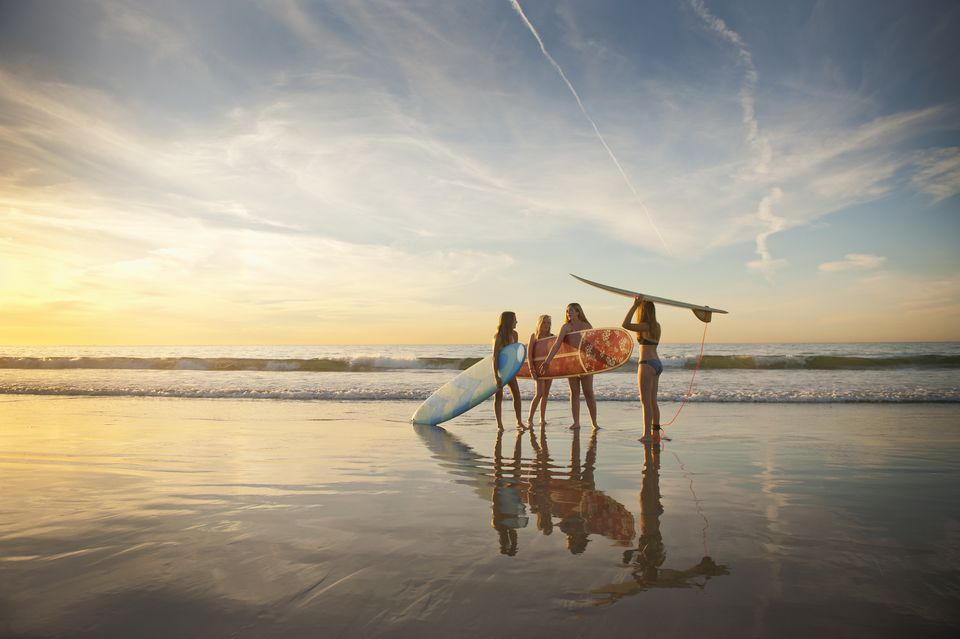Teen girls going surfing in late afternoon