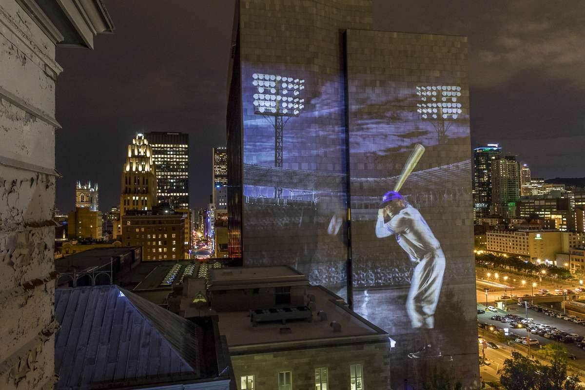 A projection of a baseball player on a building for Cite Memoire