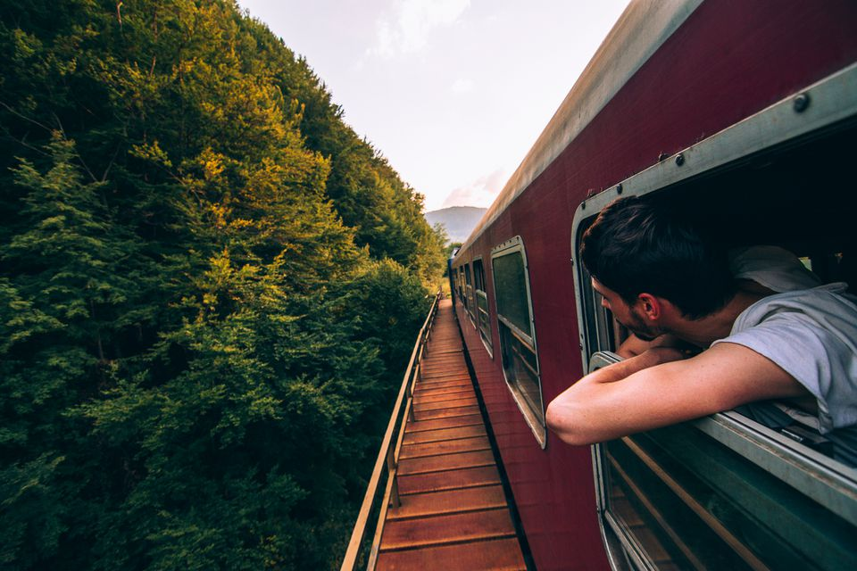 Hombre en el tren con la cabeza fuera de la ventana