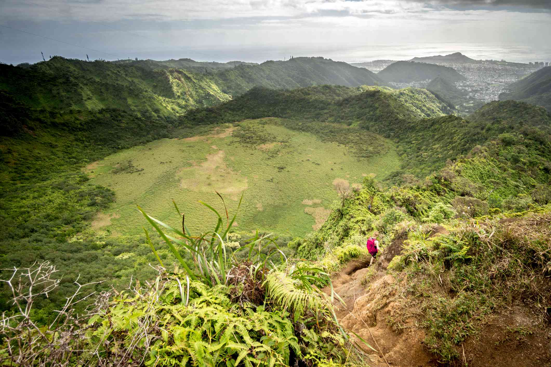 A woman with a backpack hikes along the Ka'au Crater Trail