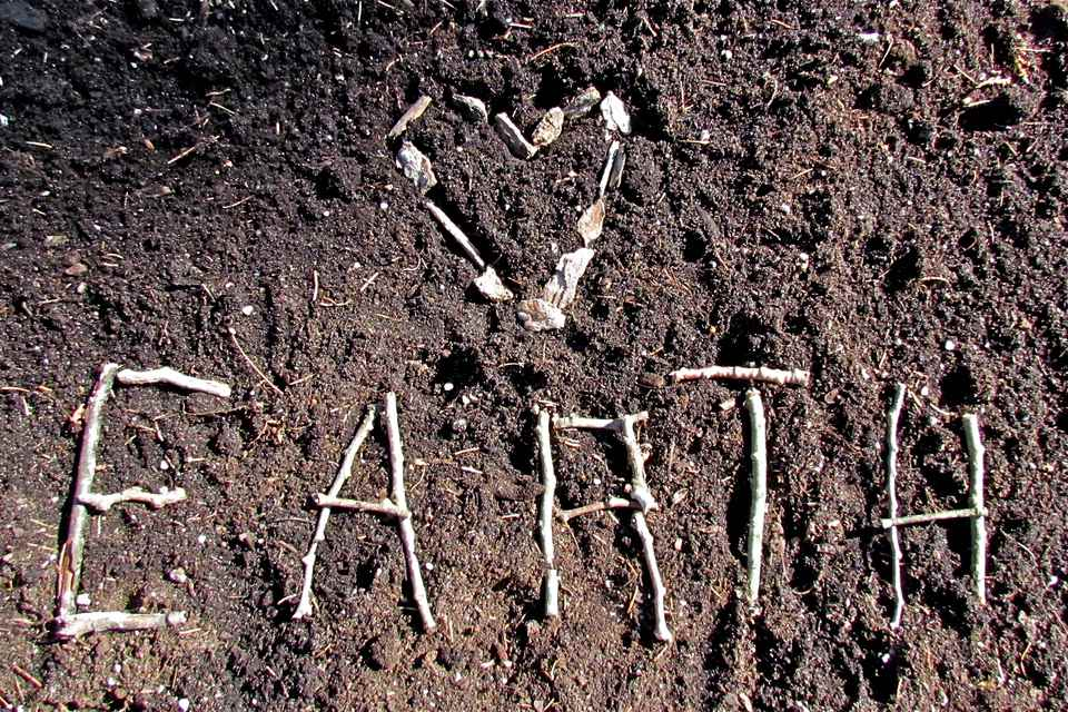 Earth spelled out with twigs in the dirt