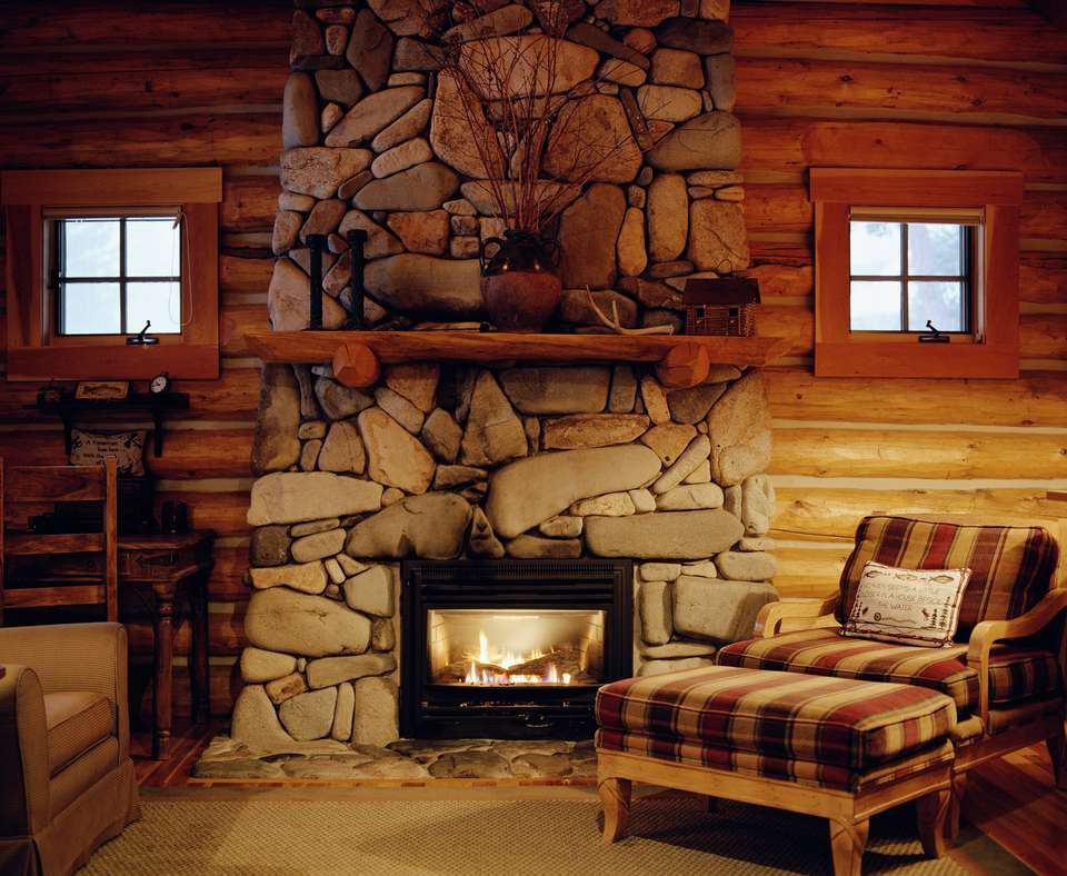 Armchair beside stone fireplace in log cabin