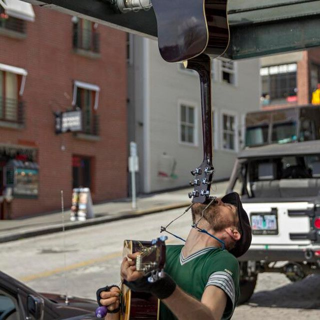 Busker balancing guitar on his chin at Pike Place Market