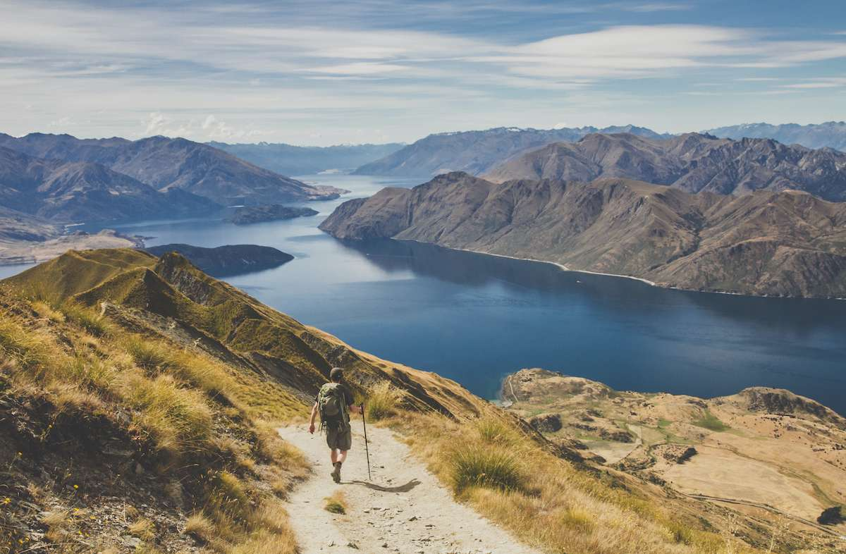 A hiker walks down a trail with a large lake and mountains in the distance