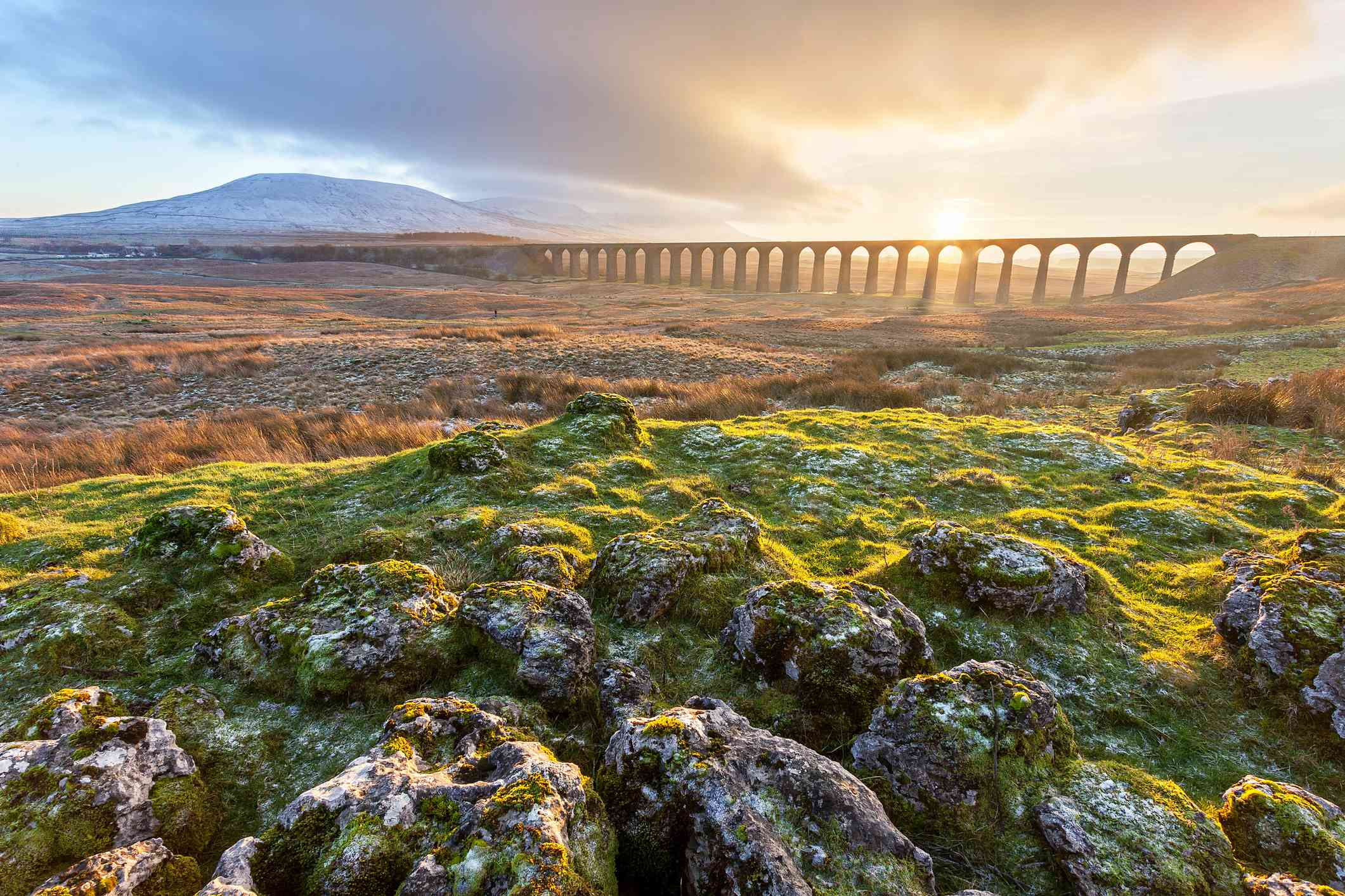 Sunset over Ribblehead viaduct on the Settle to Carlisle line in the Yorkshire Dales National Park. Surrounded by the three peaks of Ingleborough, Whernside and Pen-y-ghent.