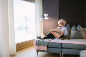 Woman reading comfortably in hotel room