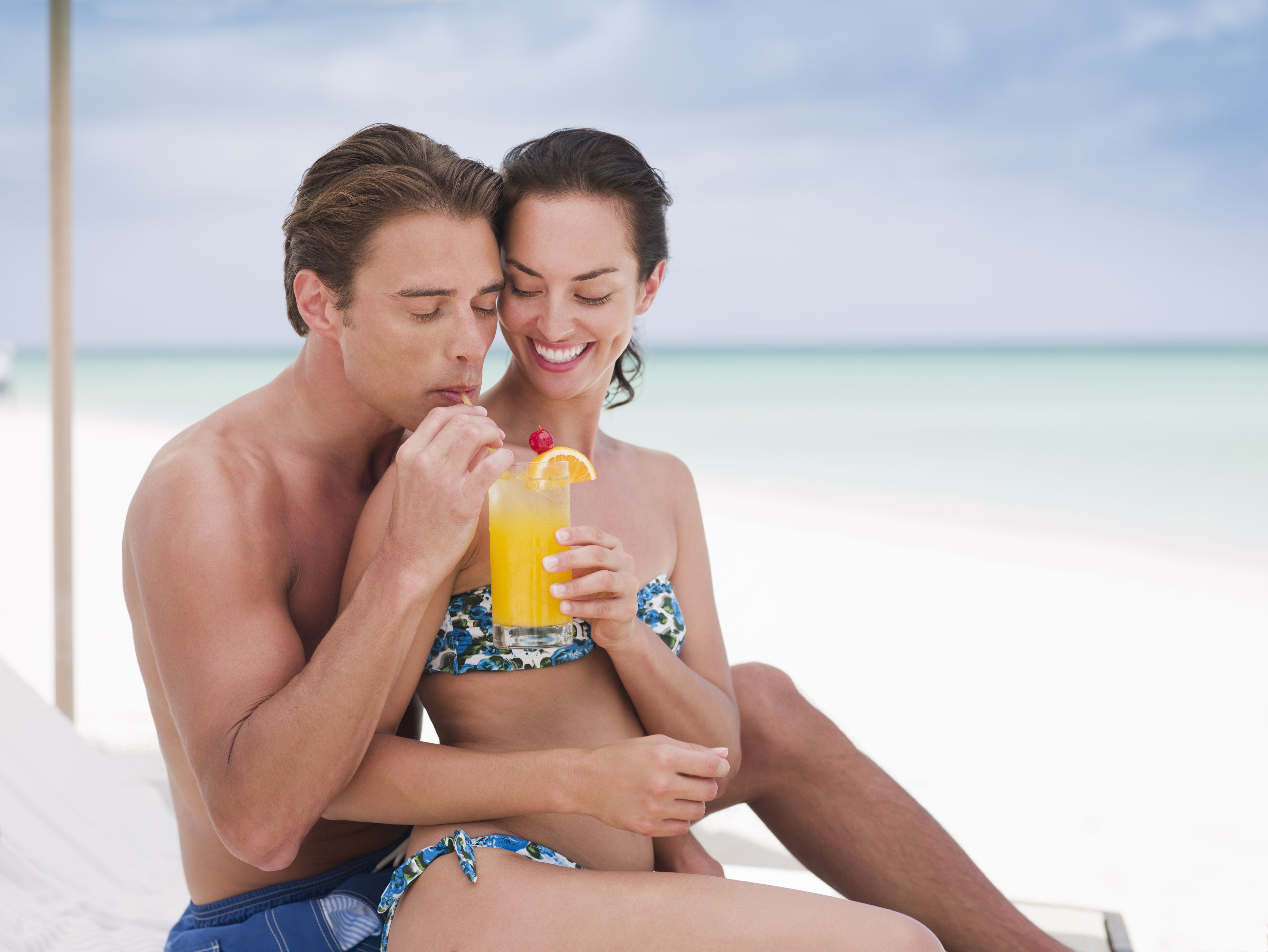Couple sharing cocktail on beach