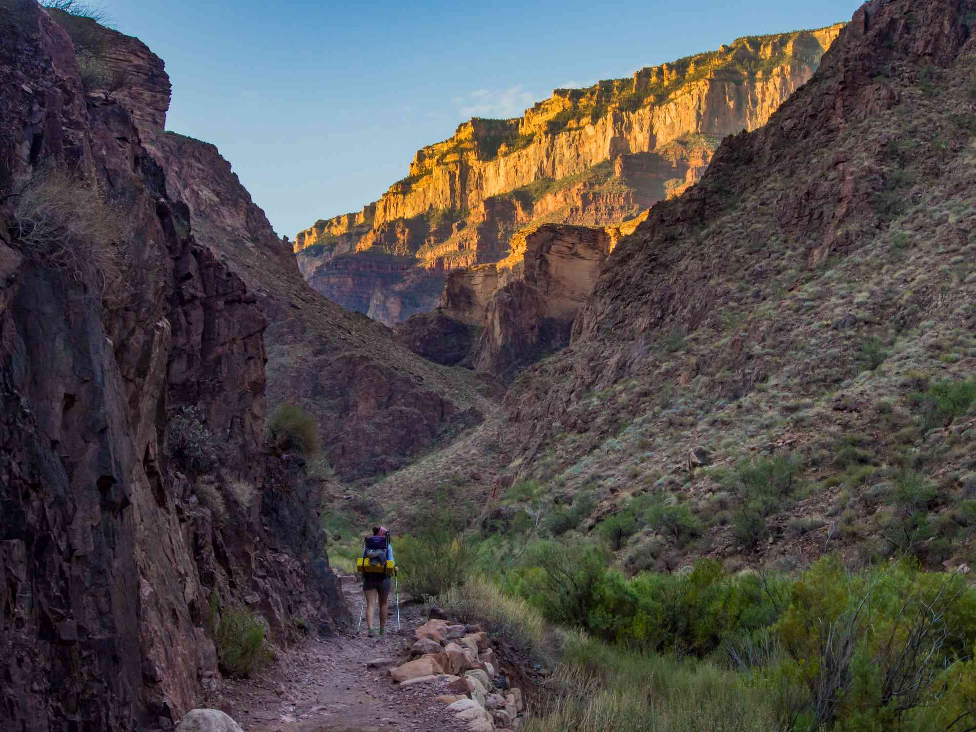 Backpacker On The Bright Angel Trail In The Grand Canyon, Sunlight On The Upper Canyon Walls.