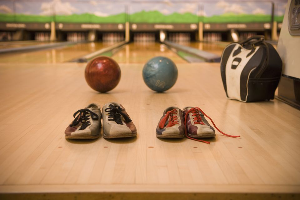 Two Bowling Balls and Bowling Shoes Resting on Bowling Alley Lane with Bowling Ball Bag
