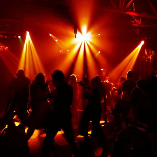 People dancing under orange lights inside Enigma Bar, St. Petersburg, Florida