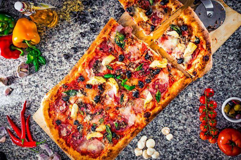 pizza on a cutting board with ingredients scattered