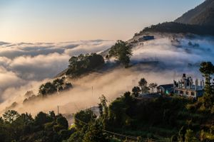 mountains covered with misty clouds, trees and a couple of buildings