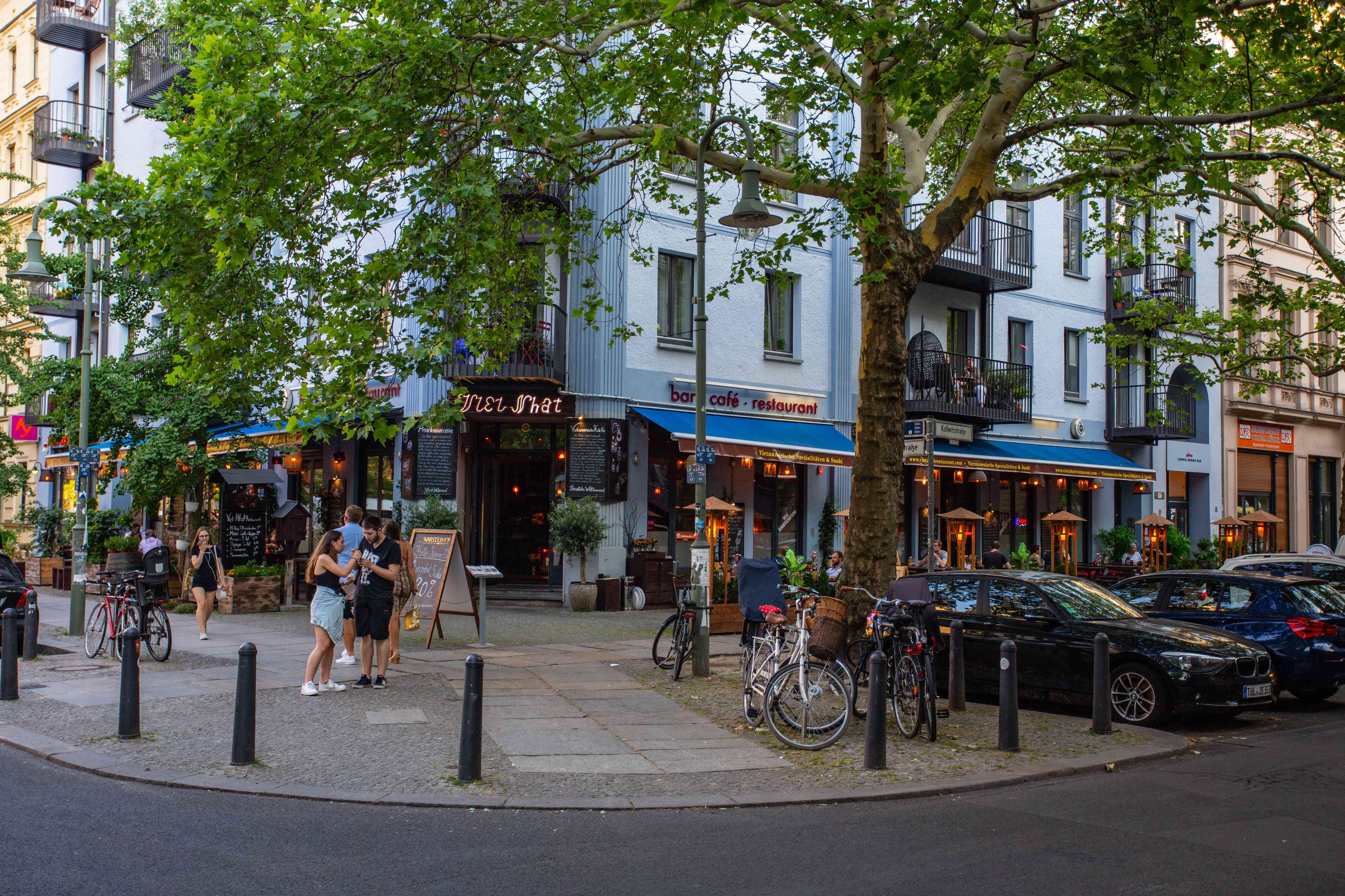 A street corner with colorful shop fronts and people hanging out