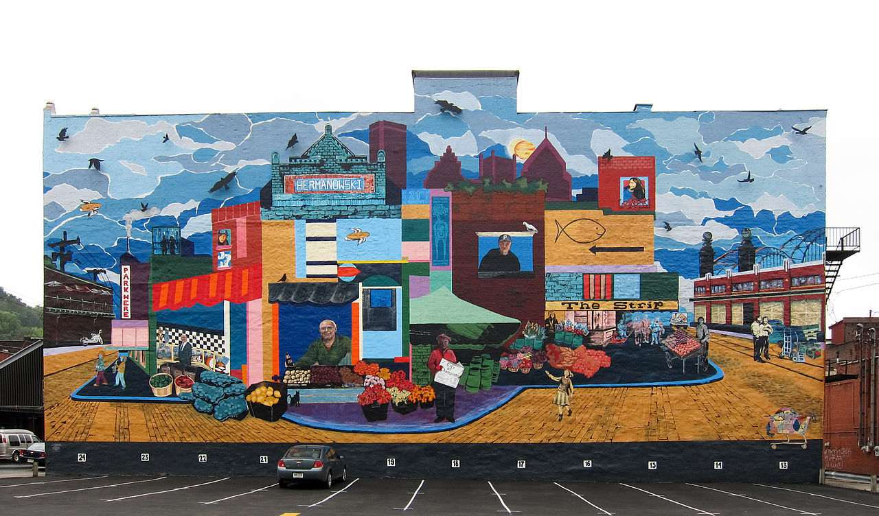 """English: The """"Strip Mural"""" on the side of the Hermanowski Building by Carley Parrish and Shannon Pultz at 1907 Penn Ave in Strip District in Pittsburgh. This large mural depicting the neighbourhood dresses up what otherwise would be a big dull grey wall."""