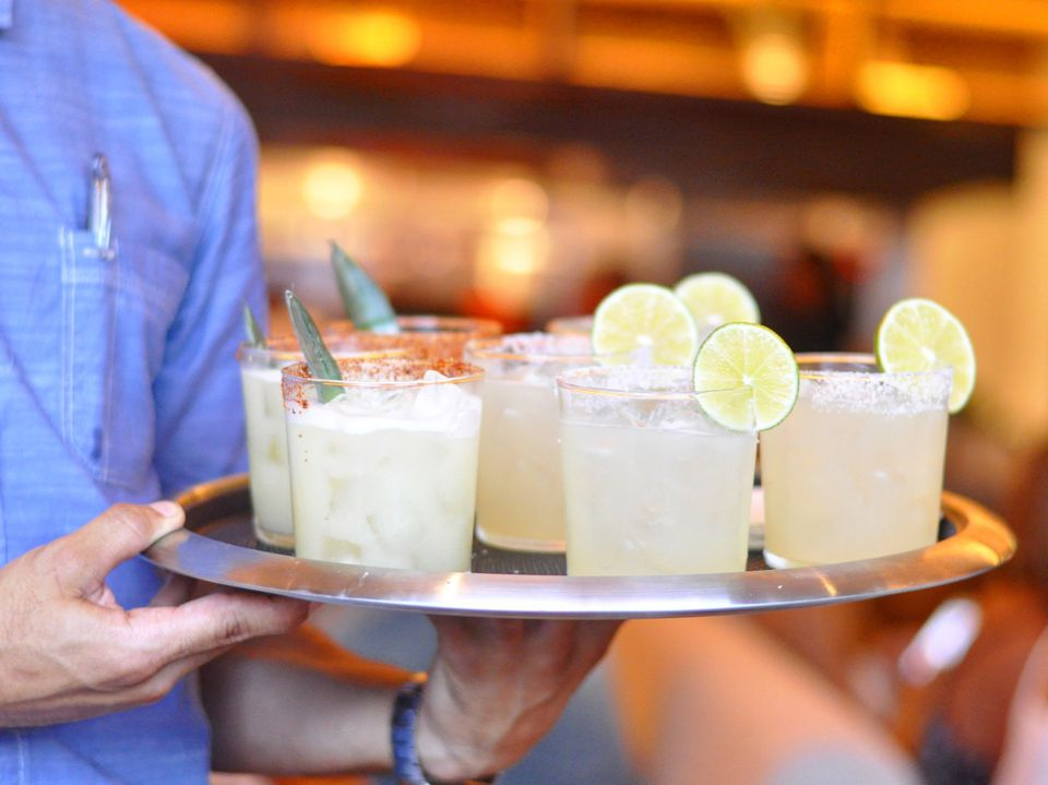 a tray of margaritas being carried by a waiter