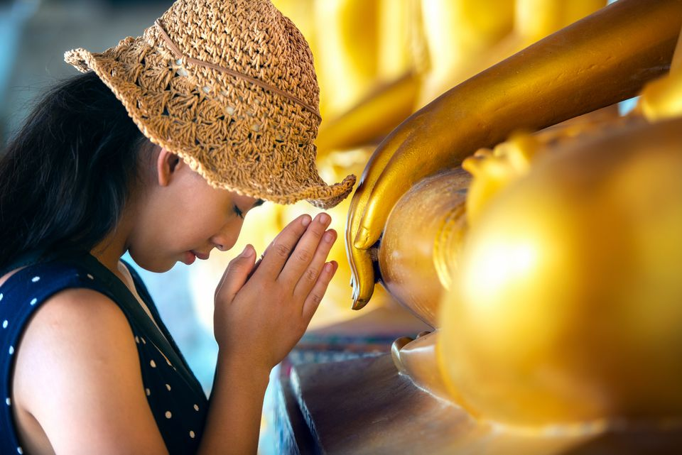 Tourist paying respect to Buddha in Thailand