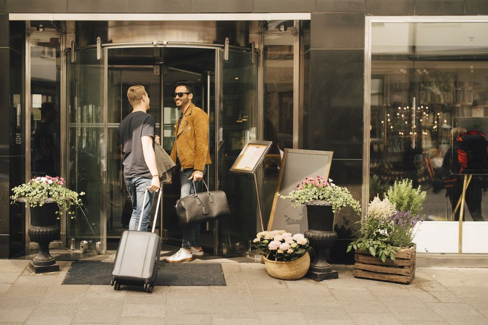 Friends talking while standing at doorway of hotel in city