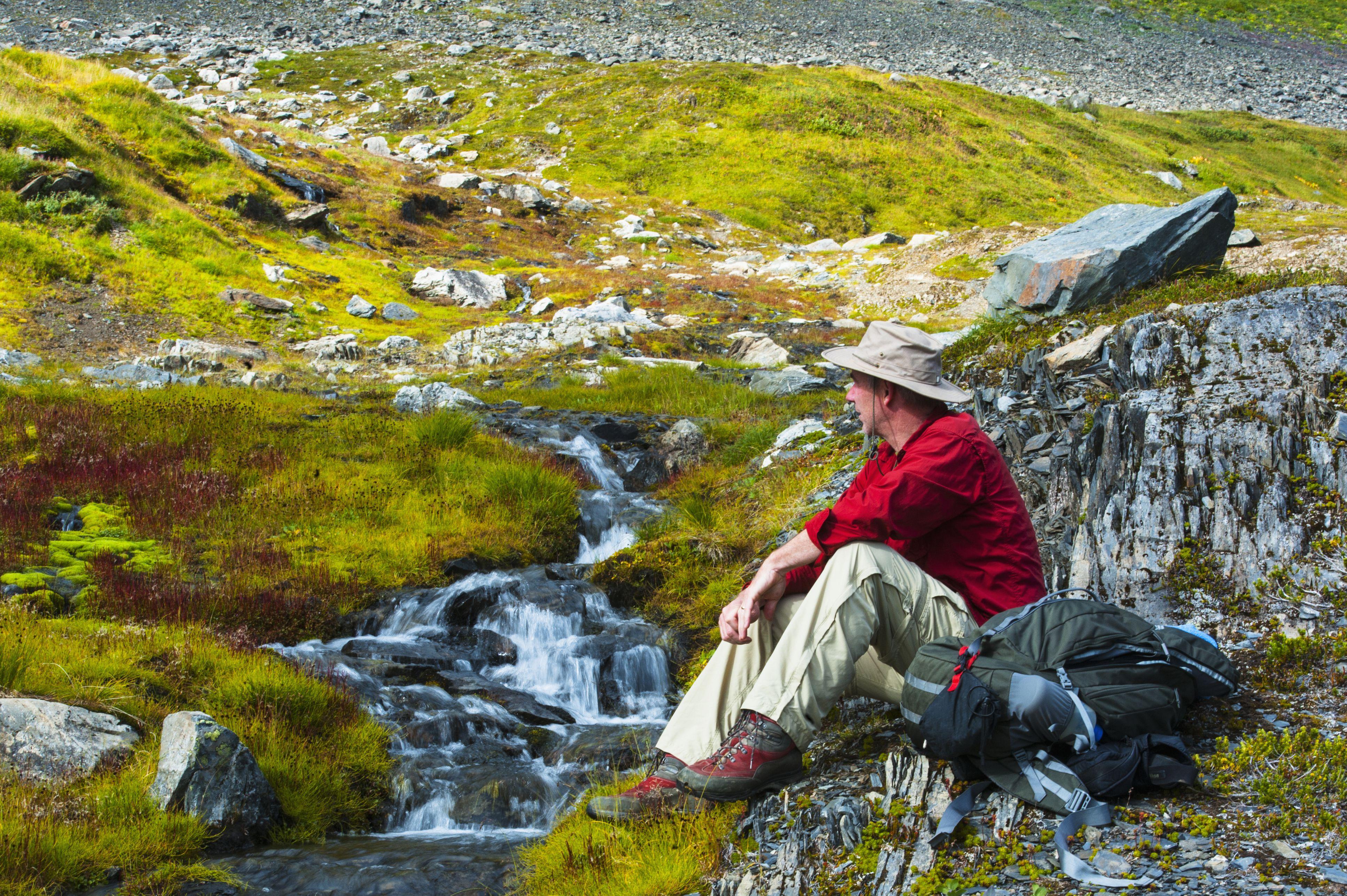 A man sitting next to a stream, Kenai Fjords National Park, Kenai Penninsula, Southcentral Alaska