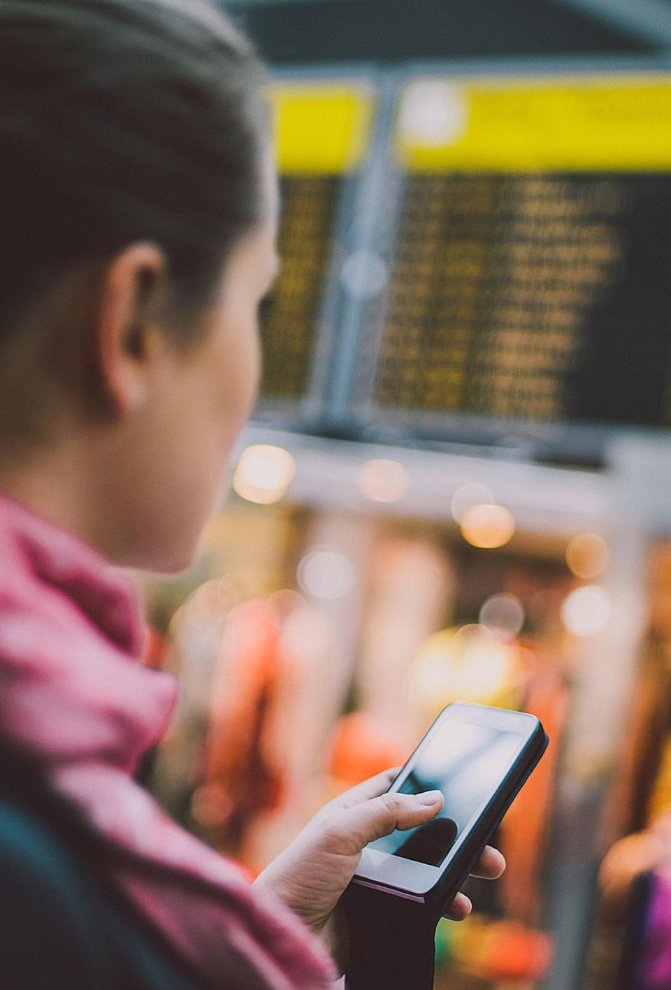 Woman using cell phone to check schedule of flights