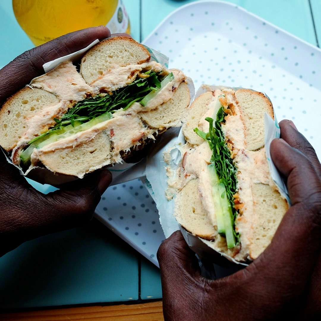 dark-skinned pair of hands holding two halves of a bagel sandwich with lettuce, avocado, and cream cheese