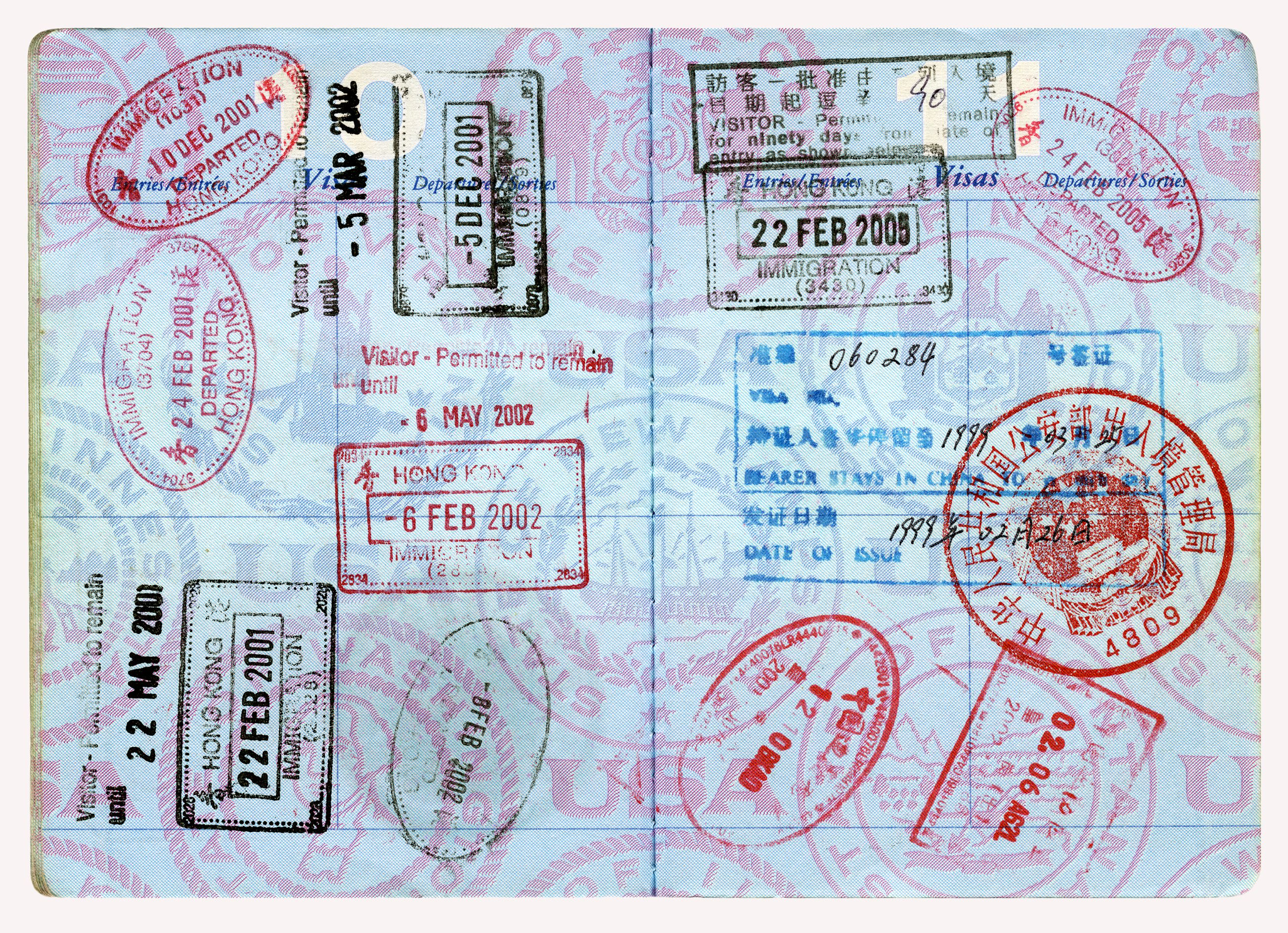 Open US Passport with several visa stamps in red, black, and blue ink