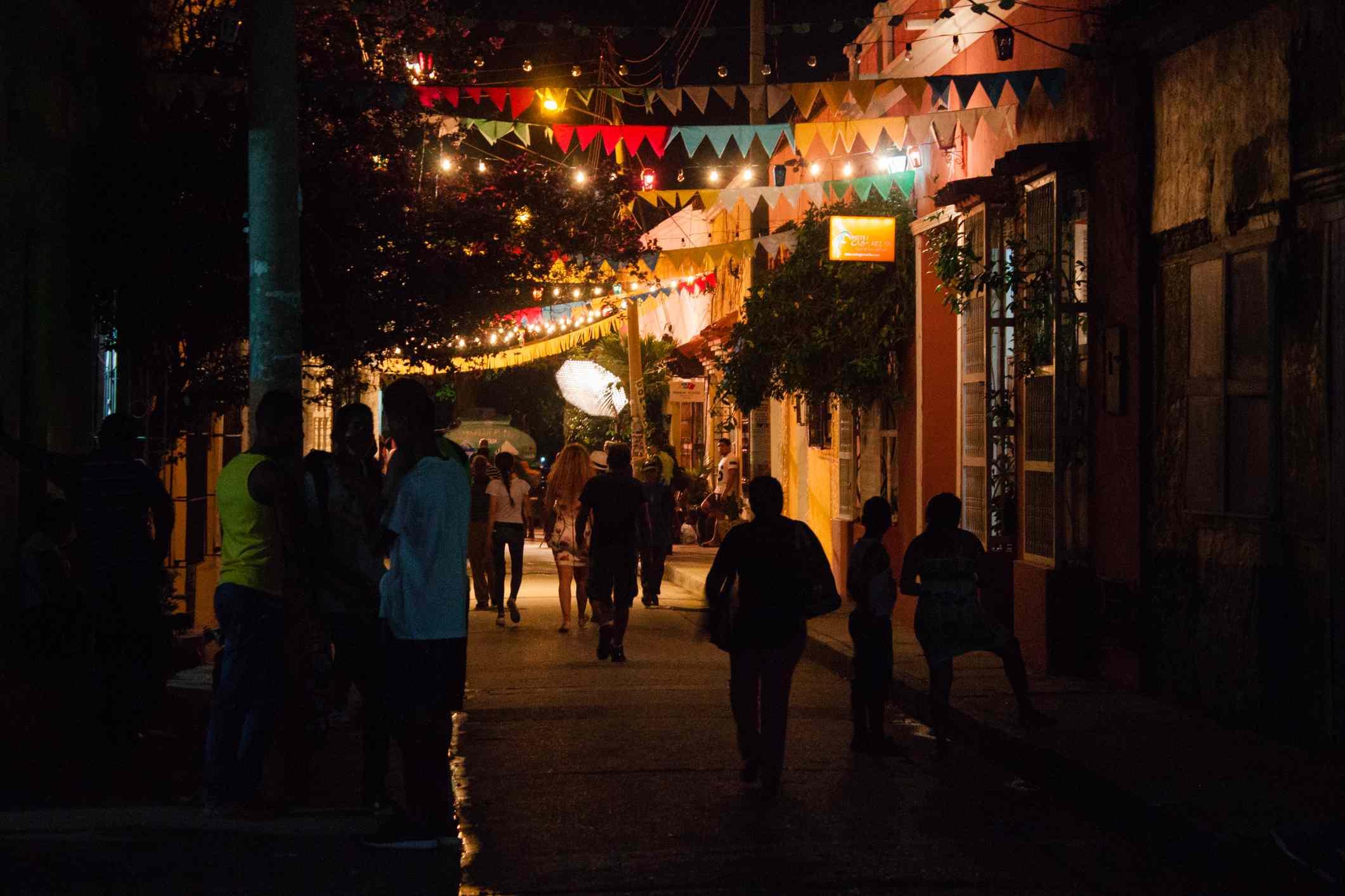 People Walking On Illuminated Street At Night in Cartagena