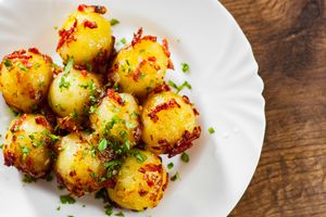 Fresh potato dumpling in white plate on wooden table background